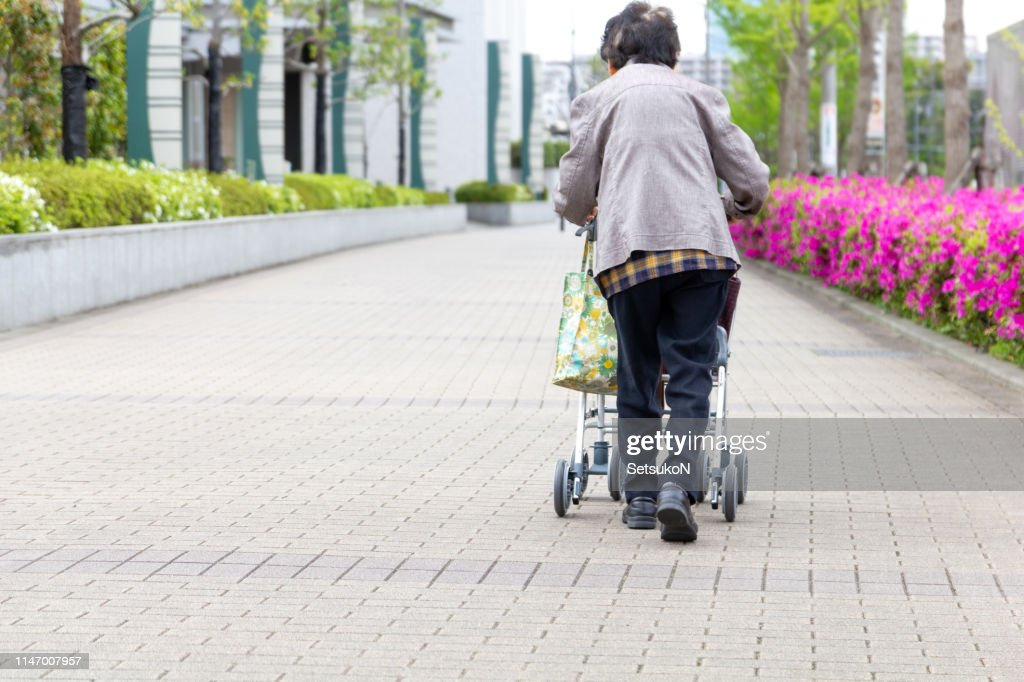 Elderly person with walking auxiliary instrument. : Stock Photo
