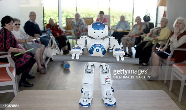 """Elderly persons look at """"Nao"""", a humanoid robot of the Institute for Intelligent Systems and Robotics , at a retirement home on April 23, 2015 in..."""