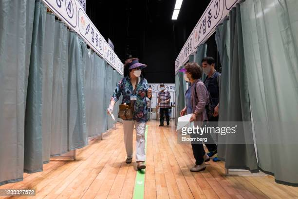 Elderly residents leave after receiving a dose of the Pfizer-BioNTech Covid-19 vaccine at a vaccination site inside the Guro Arts Valley Theater in...