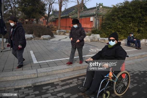 Elderly residents wear face masks as they walk near Houhai lake in Beijing on February 12, 2020. - The death toll from the COVID-19 coronavirus...