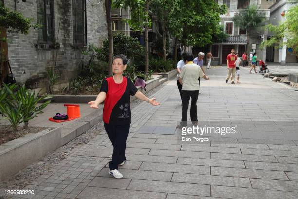 Elderly retired Chinese people do tai chi in a public park with people passing by one woman pushing a baby stroller ahead of her Liwan Lake Park...