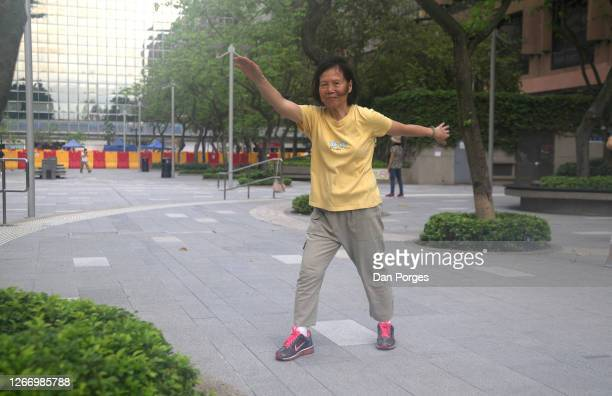 Elderly retired Chinese woman does tai chi in a public area early in the morning Hong Kong China May 6 2016