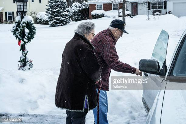 Elderly Senior Adult Couple Entering Car in Winter Snow Storm
