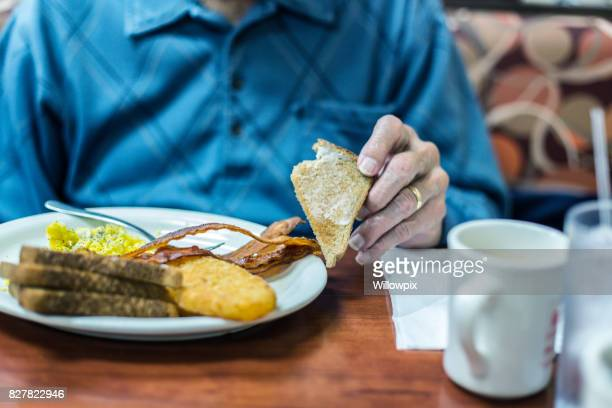 Elderly Senior Adult Man Breakfast Diner Holding Toasted Bread