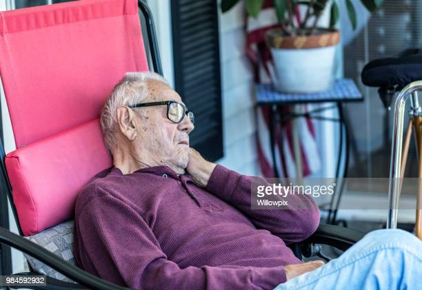 elderly senior adult man sleeping on home front porch - reclining chair stock photos and pictures