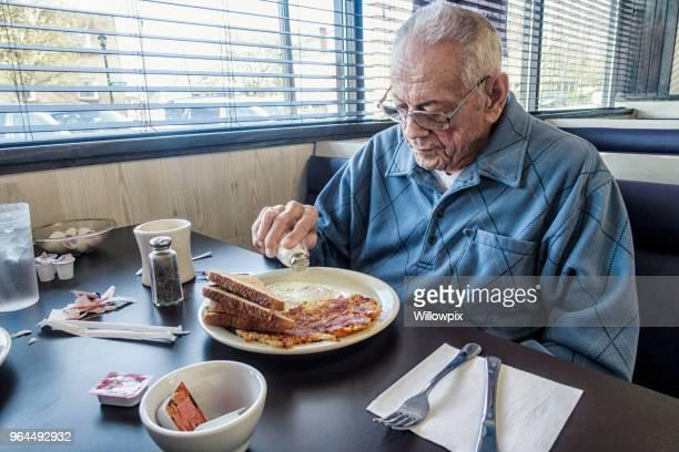 Elderly Senior Adult Man Sprinkling Table Salt on Breakfast Eggs