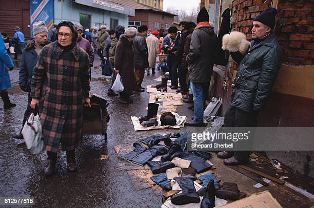 Elderly shoppers walk through a wet street at the Tichinsky Market where poor Soviet citizens of all generations sell clothing and other goods in a...