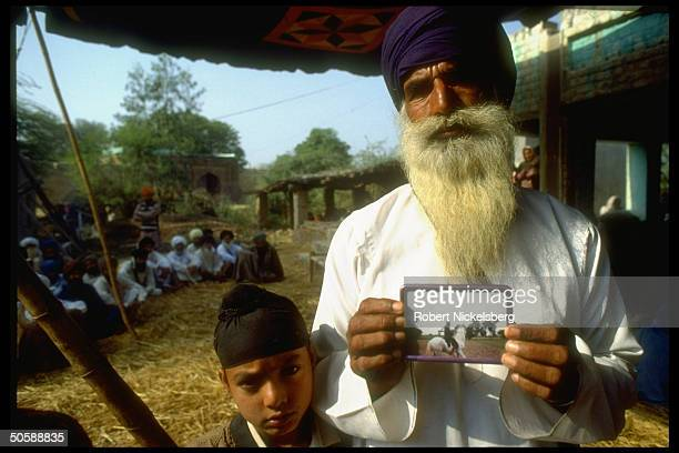 Elderly Sikh w. Pic of his dead militant son, killed in clash w. Authorities, w. His grandson at temple held bhog , in violence torn Punjab, India.