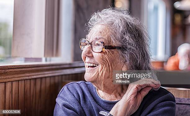 Elderly Smiling Woman With Dementia Looking Out Restaurant Window