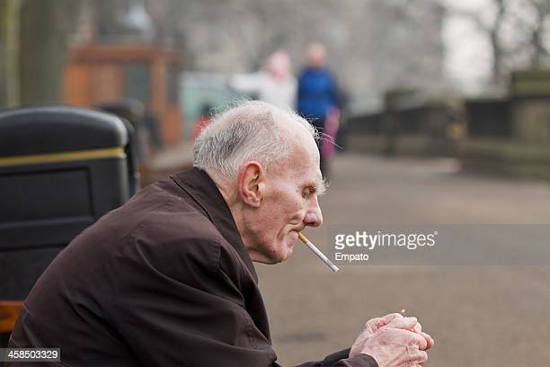 elderly smoker lights his cigarette. - editorial stock pictures, royalty-free photos & images