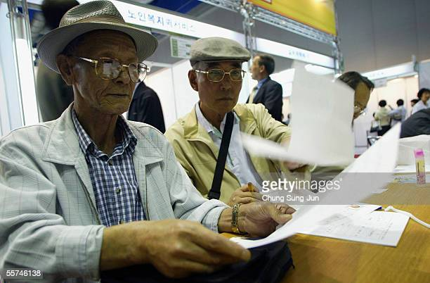 Elderly South Korean job seekers fill out job applications at an elderly persons' job fair on September 23 2005 in Seoul South Korea When the...
