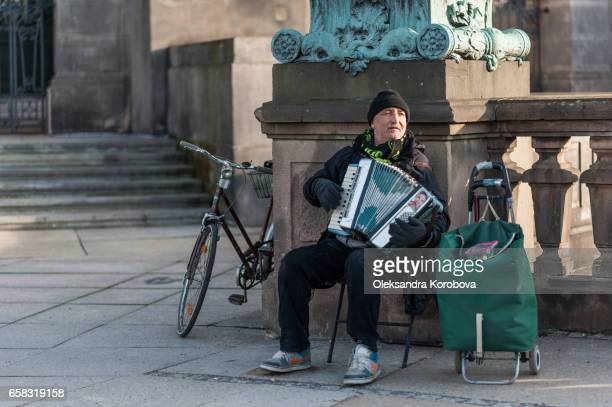 berlin, germany - december 16, 2016. elderly street performer entertaining passersby by playing an accordion on the bridge in front of the bode museum in berlin, germany. - istock photos et images de collection