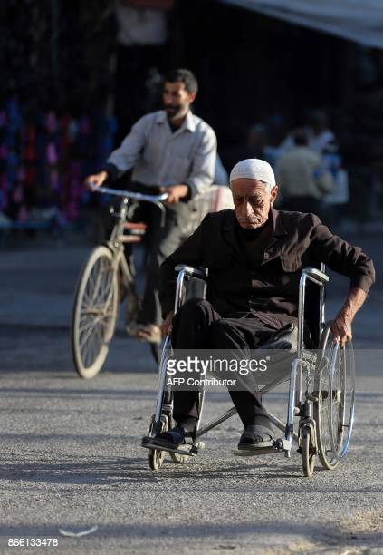 A elderly Syrian man on a wheelchair makes his way at a street in Douma a rebelheld town on the outskirts of the capital Damascus on October 24 2017...