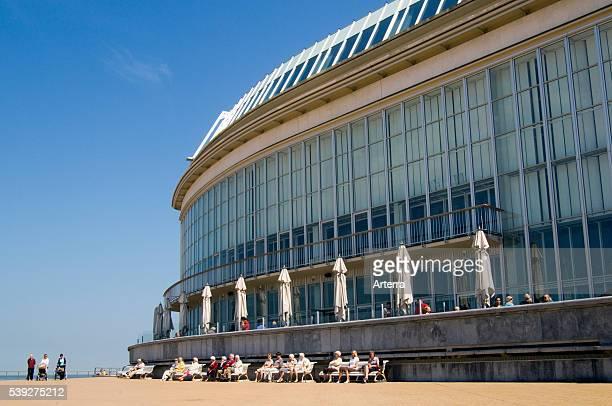 Elderly tourists sunning on sea dyke promenade behind the Casino Kursaal at seaside resort Ostend / Oostende Belgium