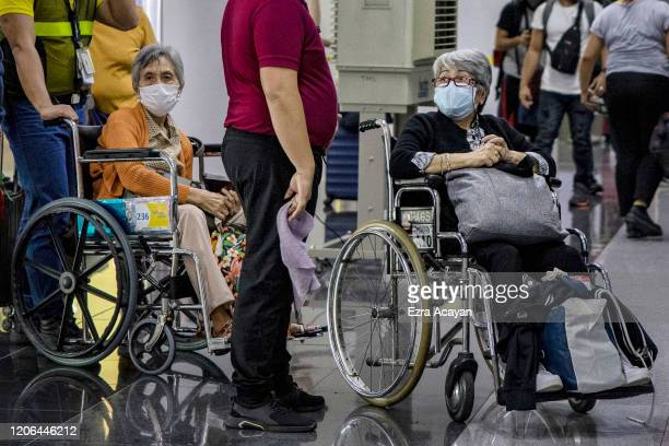 Elderly travelers are seen wearing facemasks as they queue at an immigration counter upon arrival at Ninoy Aquino International Airport on March 10...