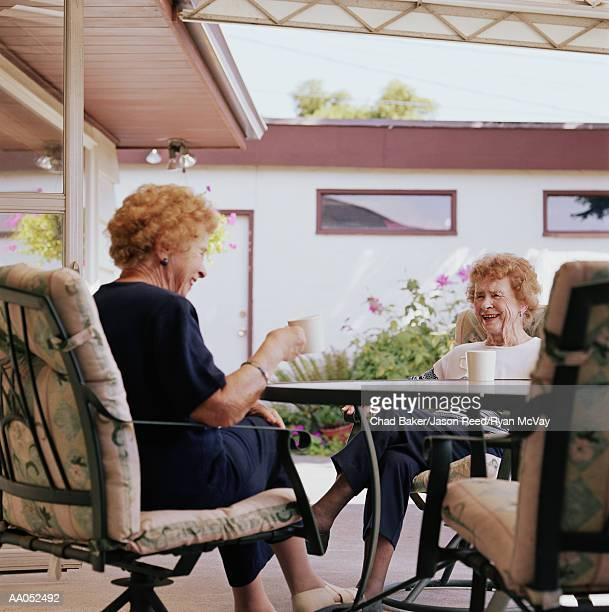 Elderly twin sisters sitting at table drinking coffee, laughing