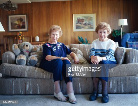 Elderly twin sisters sitting on sofa, smiling, portrait