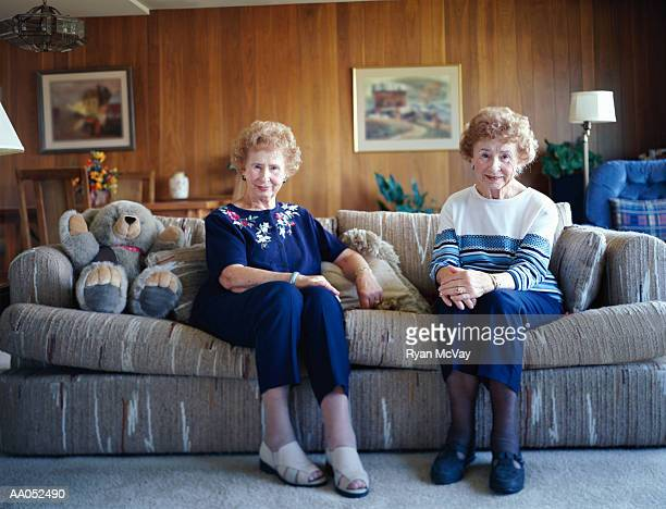elderly twin sisters sitting on sofa, smiling, portrait - zus stockfoto's en -beelden