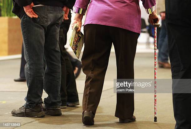 """Elderly visitors with walking stick walk through a trade fair at the """"Seniorentag 2012"""" senior citizens convention on May 3 2012 in Hamburg Germany..."""