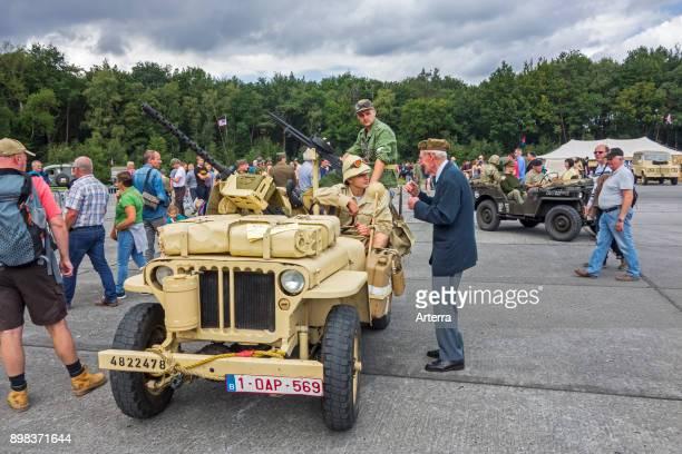Elderly war veteran talking to young WW2 reenactors in WWII SAS Willys MB jeep during World War Two militaria fair.