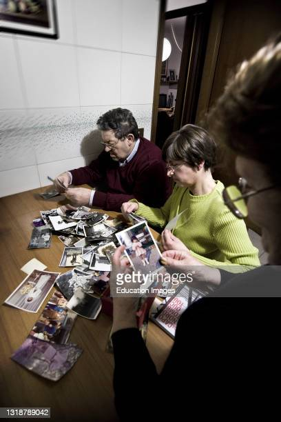 Elderly with Alzheimer's Disease Who Looks Old Photographs with Her Daughter and Wife.