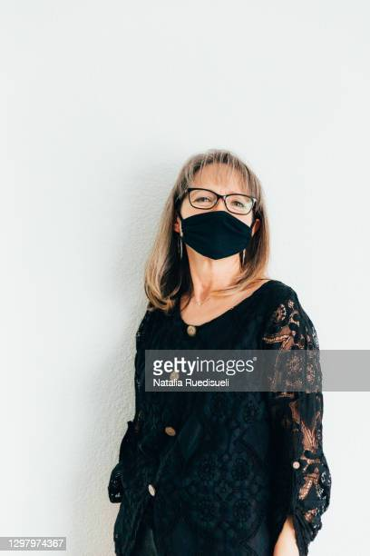 elderly woman 50-55 years old wearing a black colored mask and smiling into the camera. - 55 59 years stock pictures, royalty-free photos & images