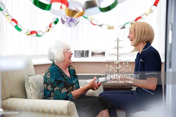 elderly woman and carer pulling Christmas cracker