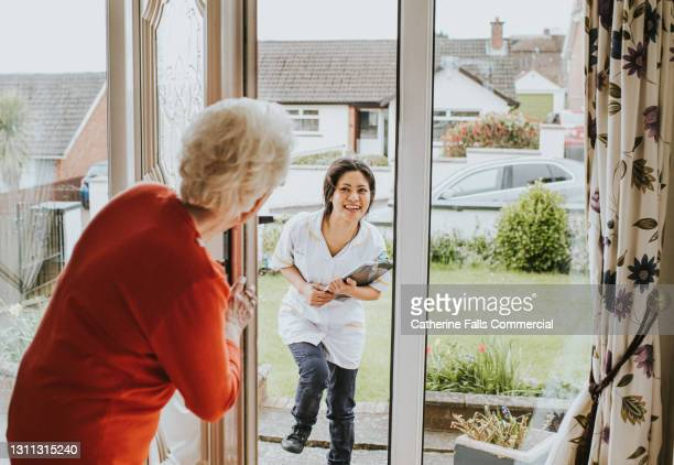 elderly woman answers the door and greets a friendly young carer - door stock pictures, royalty-free photos & images