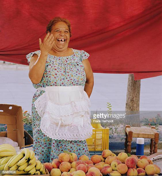 Elderly woman at fruit stall, laughing