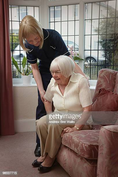 elderly woman being helped into a chair by a carer - 立ち上がる ストックフォトと画像