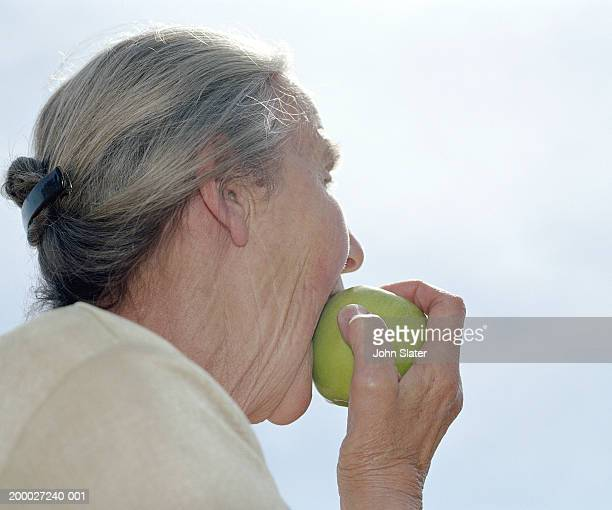 Elderly woman biting into apple, close-up