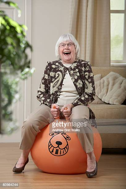 elderly woman bouncing on a space hopper - hoppity horse stock photos and pictures