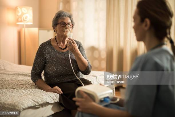 Elderly woman breathing through oxygen mask during home therapy.
