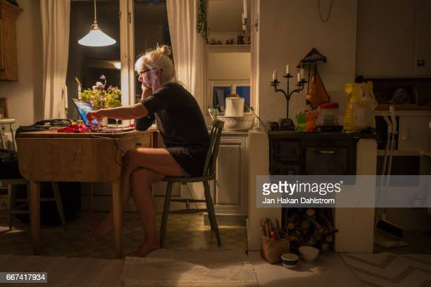 Elderly woman by table in small cottage