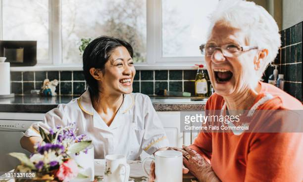 elderly woman cackles beside a giggling young care assistant - fun stock pictures, royalty-free photos & images
