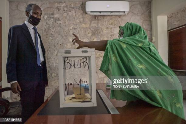 Elderly woman casts her ballot at the Ras-Dika district polling station as an electoral commission official looks on in the capital Djibouti on April...