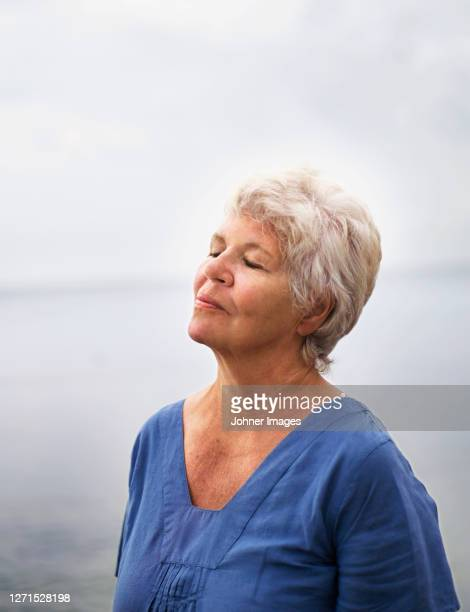 elderly woman closing her eyes and enjoying the sea - harmony stock pictures, royalty-free photos & images