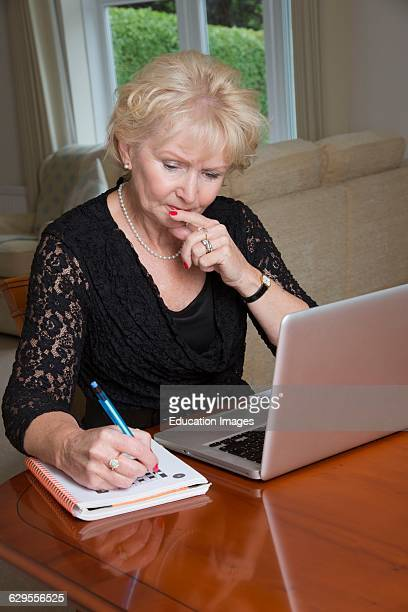 Elderly woman completing a crossword puzzle using laptop computer.