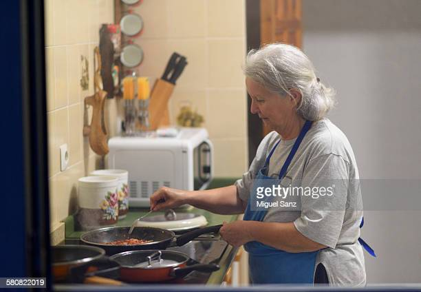 Elderly woman cooking in the kitchen