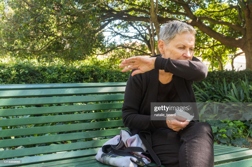 Elderly woman coughing into elbow and holding tissue outdoors : Stock Photo
