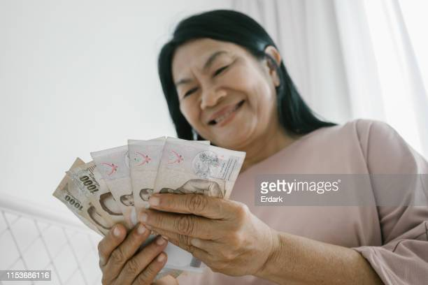 elderly woman counting thai money - grandma invoice stock pictures, royalty-free photos & images