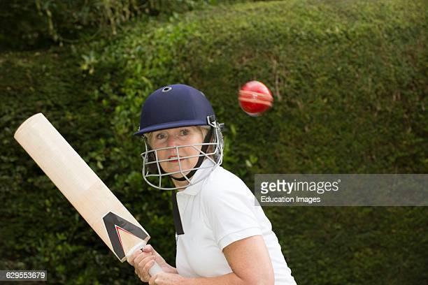 Elderly woman cricketer wearing helmet playing cricket