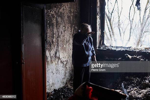 A elderly woman cries inside her burned apartment in the area near a chemical plant which has suffered artillery shellings on February 09 2015 in...