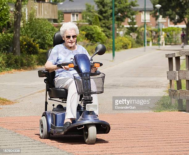 elderly woman driving mobility scooter down quiet street - mobility scooter stock photos and pictures