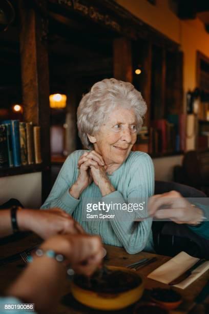 Elderly woman enjoying British Pub Lunch with Family