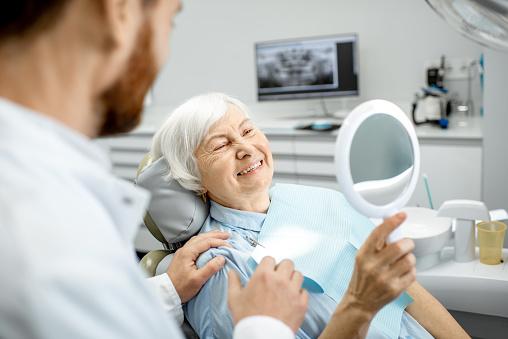 Elderly woman enjoying her smile in the dental office 1088392714