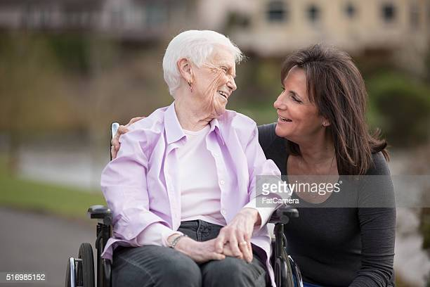 Elderly woman excersising outdoors with her caregiver