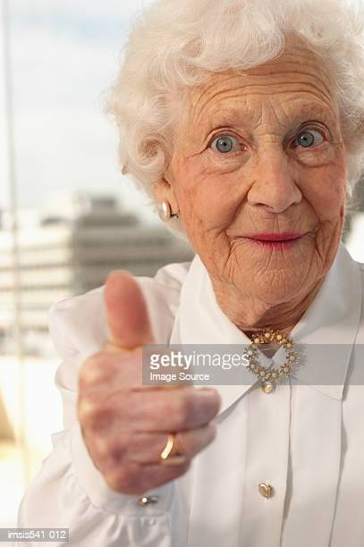 elderly woman giving the thumbs up - brooch stock pictures, royalty-free photos & images