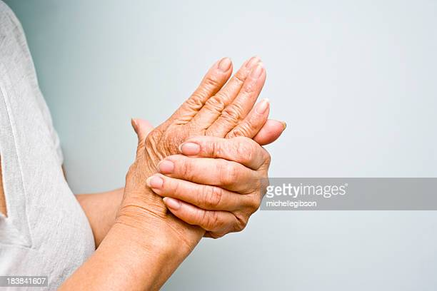 elderly woman grasping arthritic hands - pijn stockfoto's en -beelden