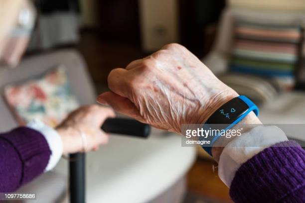 elderly woman hand and detail of the smartwatch - internet delle cose foto e immagini stock